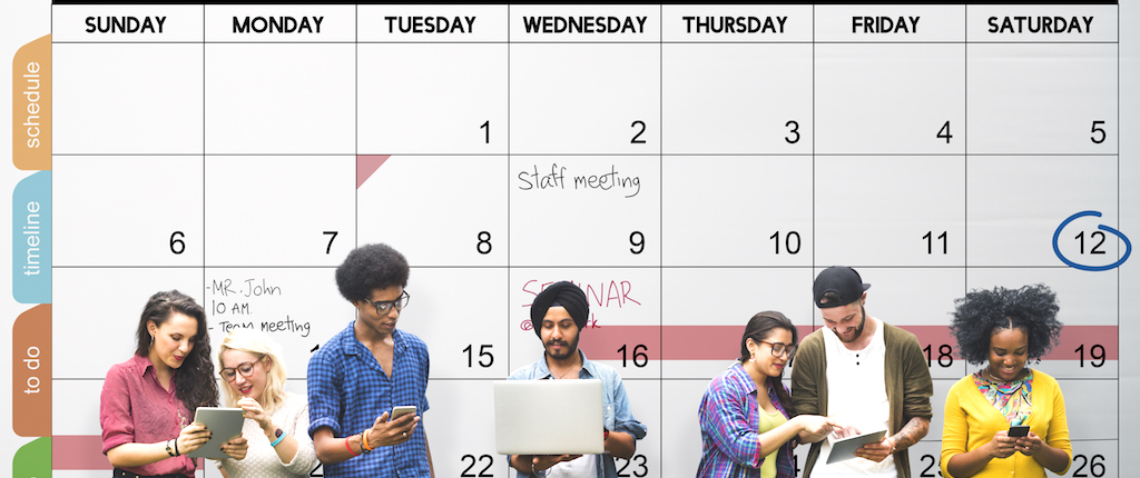 People standing in front of a calender