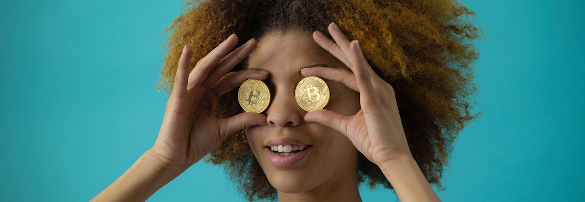 Woman holding coins up to her eyes