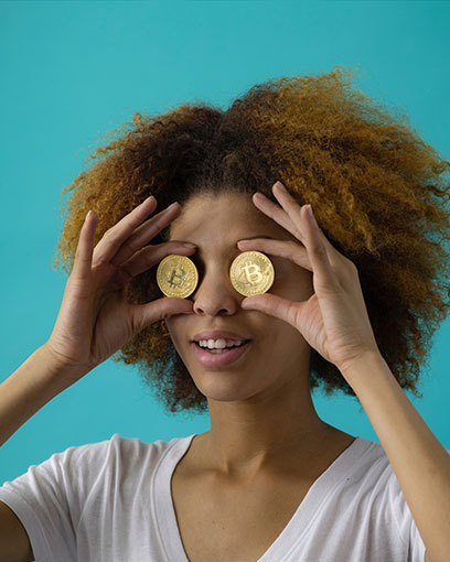 Young woman holds coins over her eyes
