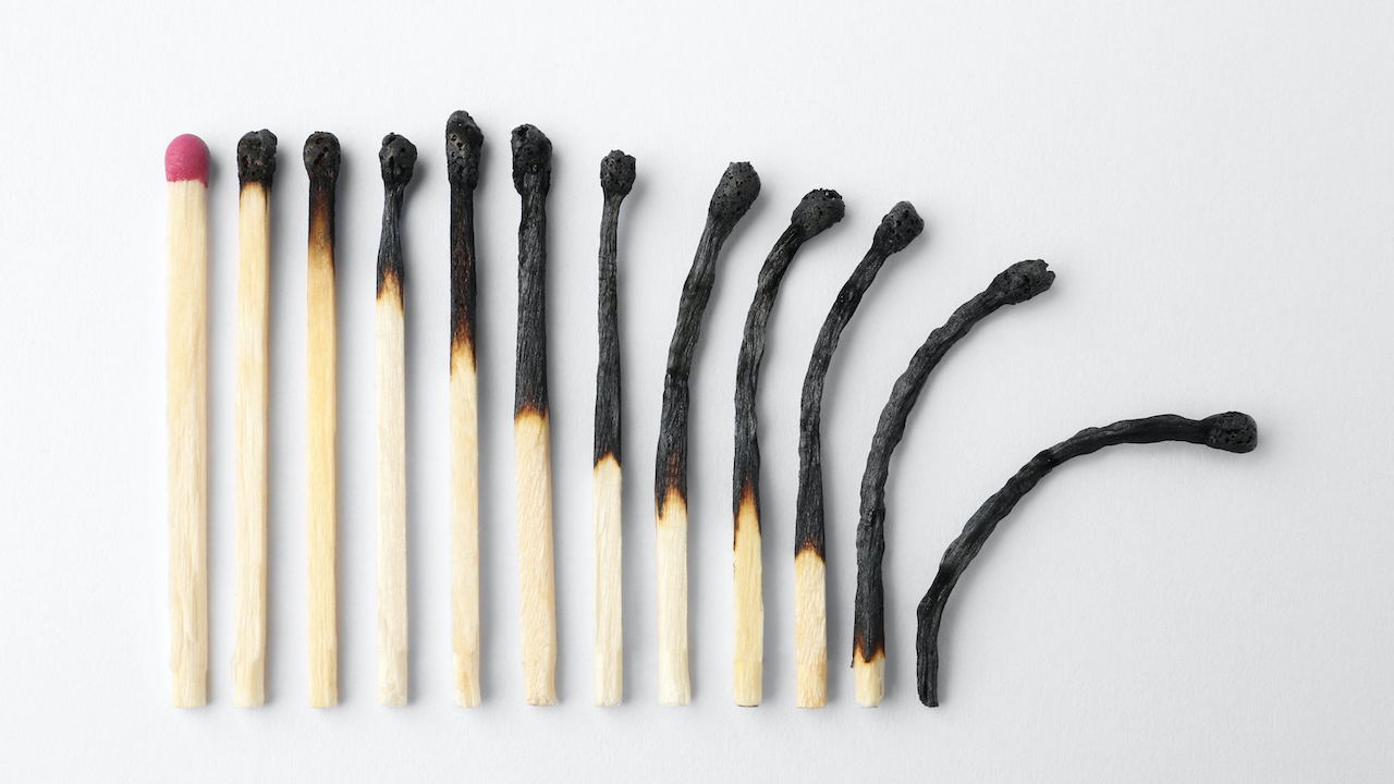Row of burnt matches and whole one on white background,